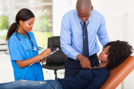 african american doctor and nurse examining female patient on examining couch photo