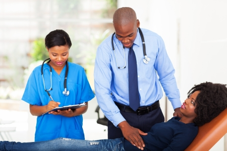 african doctor and nurse examining female patient in office