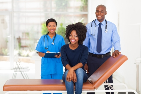 african woman sitting on doctor's examining bed with her doctor and nurse on background photo