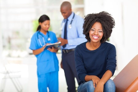 checkup: pretty young african woman sitting on examining bed and waiting for medical examination  Stock Photo