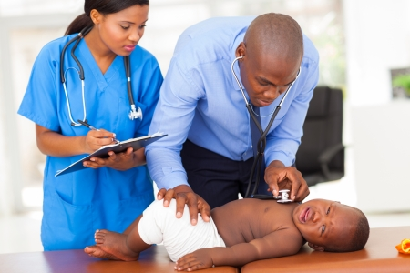 sick baby: african male pediatrician with nurse assistant examining a child in his office
