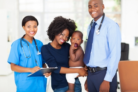 smiling pediatric medical professionals with african mother holding her baby photo