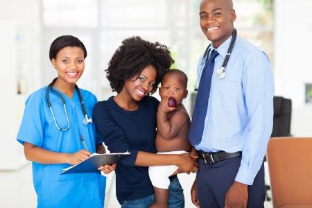 medico pediatra: sonriente pedi�tricos profesionales m�dicos con la madre africana cargando a su beb�