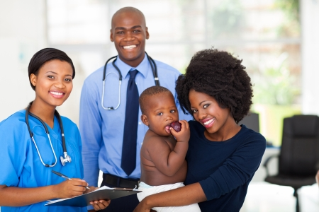 paediatrician: happy afro american mother holding her baby boy after checkup with nurse and doctor