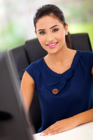 work station: pretty female office worker by her work station