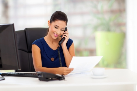smart young businesswoman on the telephone and reading report photo