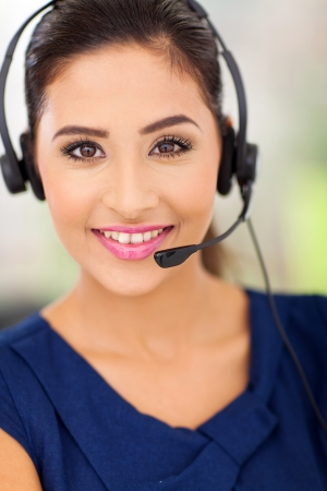 Closeup portrait of a happy young call centre employee smiling with a headset  photo