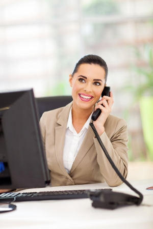 pretty business woman answering telephone in office Stock Photo - 18983641