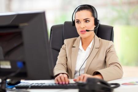 Operador del centro joven y bella mujer llamada con el auricular en la oficina