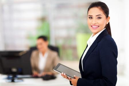 obreros trabajando: hermosa empresaria moderna que sostiene Tablet PC con su colega en el fondo