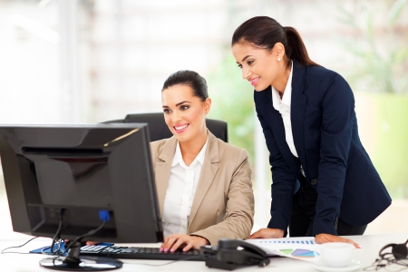 business attire: attractive business women working using computer Stock Photo