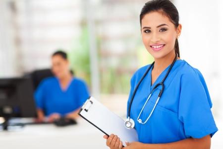 Office uniforms: enfermera practicante joven sosteniendo un portapapeles