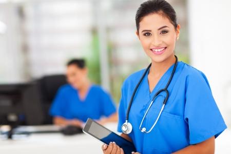 doctor verpleegster: aantrekkelijke jonge vrouwelijke verpleegkundige die tablet-computer op de werkplek