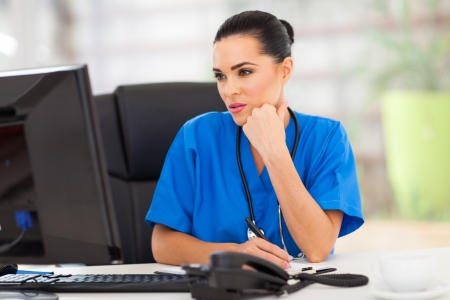nurse computer: thoughtful medical doctor looking at computer screen in office