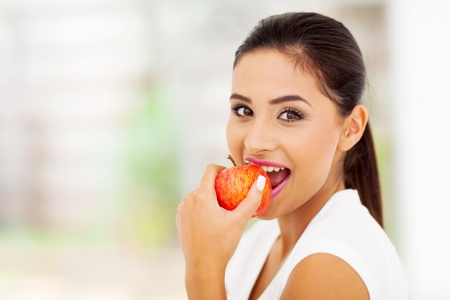 eat: beautiful young woman eating an apple