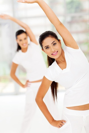 caucasian woman stretches her body for fitness with friend on background photo