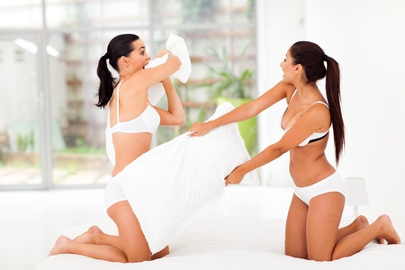 two girl friends having pillow fight in bedroom photo