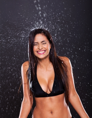 fun young woman in water splashes on black background photo