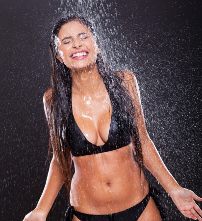 sexy young woman in water splashes on black background photo