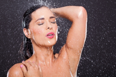 sexy young woman in shower over black background photo
