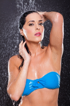 sensual young woman posing in water splashes on black background photo
