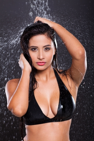 sexy young model posing in water splashes on black background photo