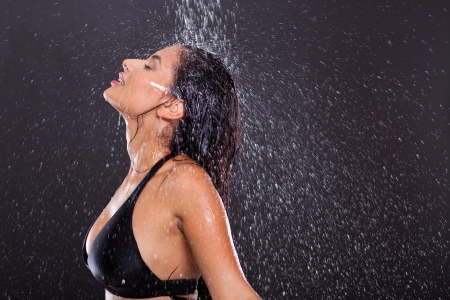 sexy girl posing in water splashes over black background photo