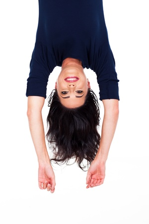 head down: pretty young woman upside down portrait on white