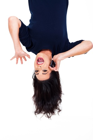 head down: fun woman talking on cellphone upside down isolated on white Stock Photo