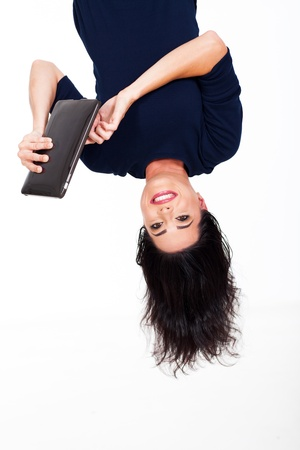 fun young woman using tablet computer upside down photo