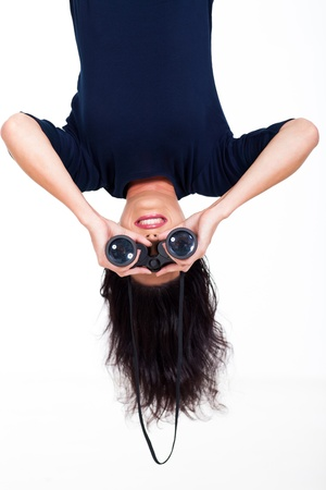 head down: upside down photo of young woman holding binoculars