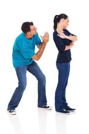pareja discutiendo: hombre pidiendo su esposa enojado sobre fondo blanco Foto de archivo