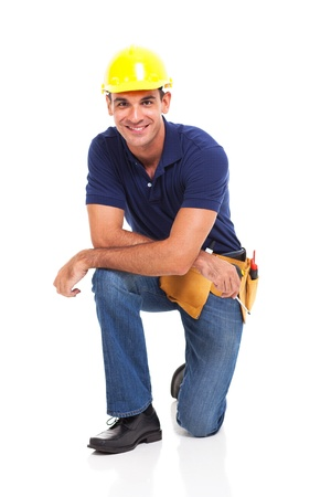 kneeling man: happy male constructor kneeling over white background Stock Photo
