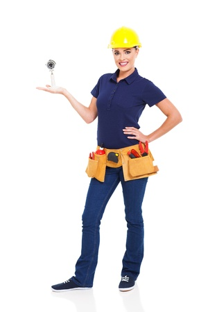 tools belt: female cctv installer presenting security camera isolated on white Stock Photo