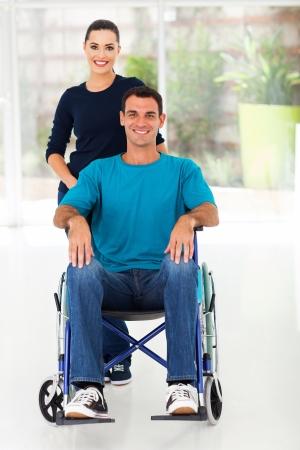 silla de ruedas: hombre discapacitado se sienta en silla de ruedas con su esposa cariñosa en casa