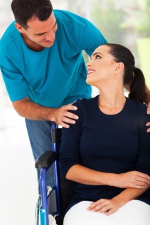 persona en silla de ruedas: amante esposo hablando con la mujer con discapacidad en el pa�s