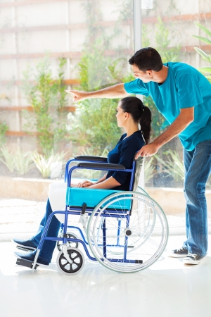 wheelchair woman: caring husband and disabled wife looking outside window at home