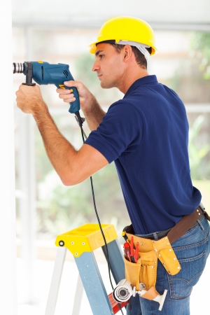 setup man: cctv camera installer drilling on the wall Stock Photo
