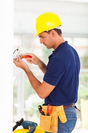 installer: security surveillance system technician installing cctv camera Stock Photo