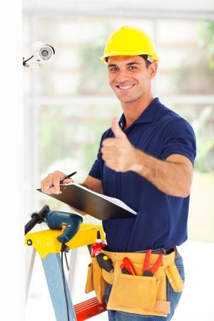 seguridad laboral: profesional de la cámara del cctv técnico pulgar hacia arriba después de la instalación