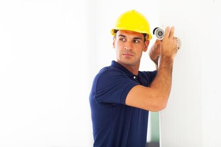 security helmet: professional cctv technician adjusting security camera angle Stock Photo
