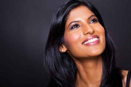 woman black background: beautiful indian woman looking up on black background