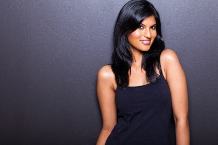 portrait of attractive female model on black wall photo