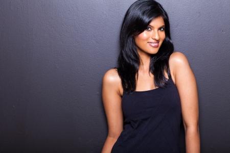 latin american ethnicity: portrait of attractive female model on black wall