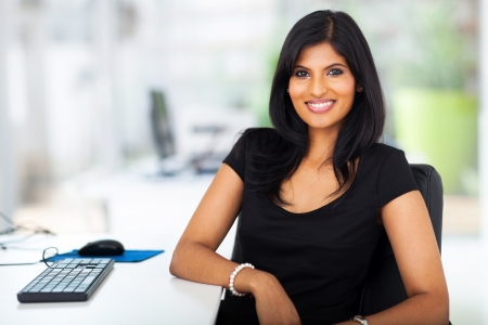 lovely young businesswoman sitting in modern office photo