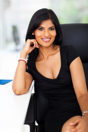 attractive young indian office worker sitting by office desk photo