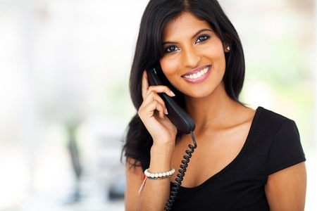 smile close up: gorgeous young businesswoman answering telephone in office