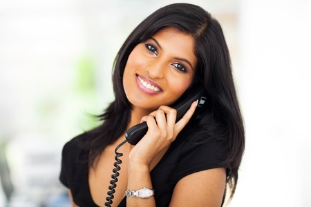 talking telephone: beautiful career woman talking on telephone in office Stock Photo