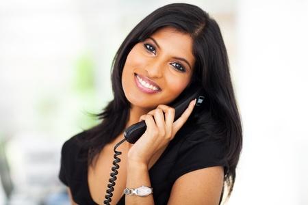 happy employee: beautiful career woman talking on telephone in office Stock Photo