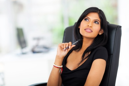 woman thinking: lovely thoughtful young businesswoman looking up